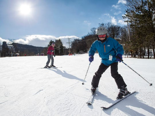 Lingling Wang, left, and husband Xiao Chen of Corning take a run before a first-time lesson on the Alpha slope at Greek Peak Mountain Resort on Sunday, January 1, 2017.   Thomas La Barbera / Correspondent Photo
