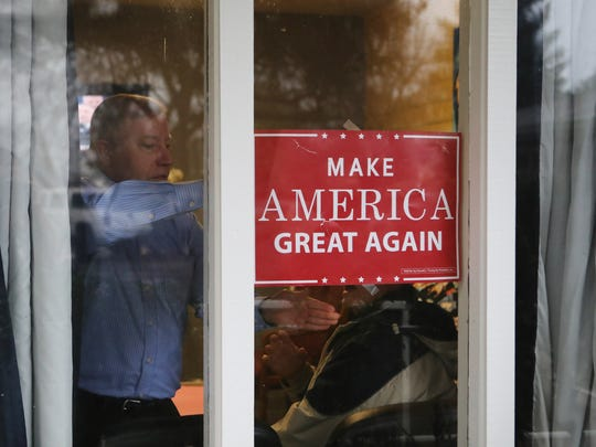 Gordon Shumate of Millville puts back a sign that fell during an inauguration party at the chiropractic office of Dr. Maria Salas in Redding. Shumate's office is next door.