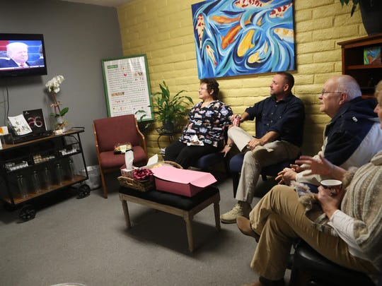 Caroline Deckness, from left, Vint Stevenson, Gary Cadd and Tomi Gibb watch the inauguration of Donald Trump on Friday during an inauguration party at the chiropractic office of Dr. Maria Salas in Redding.