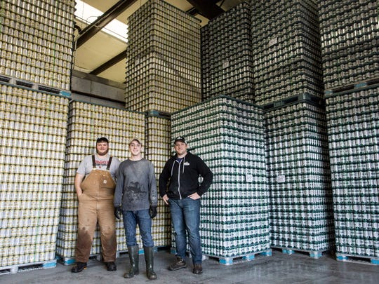 Great Flood Brewing Company co-owners, Matt Fuller, Zach Barnes and Vince Cain stand in front of a wall of beer ready to ship from their new Shelby Park brewery. 1/21/17