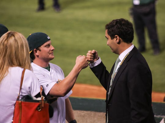 Oakland A's president Dave Kaval fist-bumps a fan while