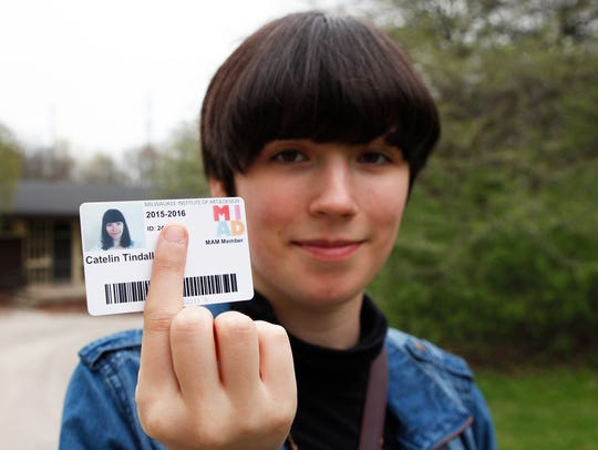 Catelin Tindall holds her expired student ID from the