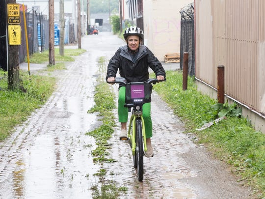 Kirby Adams takes one of the LouVelo Bikeshare cycles out for a spin along an alley in the NuLu District on East Market. 5/24/17