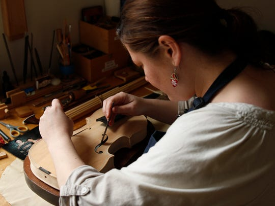 Sonja St. John inserts a note in one of her handmade