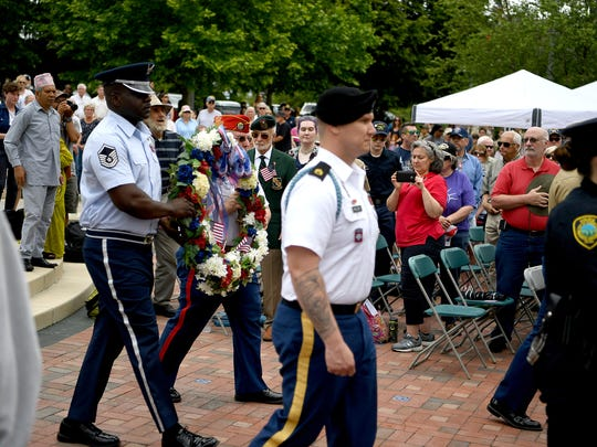 Local law enforcement carry a commemoration wreath in honor of members of the Armed Forces, Asheville and Buncombe County emergency responders Monday during the Memorial Day Ceremony in Pack Square Park in 2017.