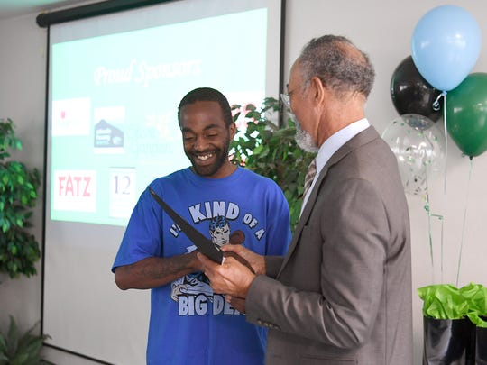 Damion Smith receives a certificate from Asheville Housing Authority CEO Gene Bell during a Family Self-Sufficiency Program graduation ceremony on Tuesday, May 30, 2017. The five-to-seven-year program is designed to improve education and job skills to cut back on welfare assistance with an ultimate goal of homeownership.