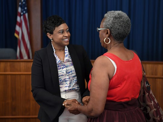 Denise Patterson talks with Elinor Earle, director of the after-school program Youth for HAND, while meeting staff and community members after being named the new superintendent of Asheville City Schools during a special school board meeting on Thursday, June 1, 2017.