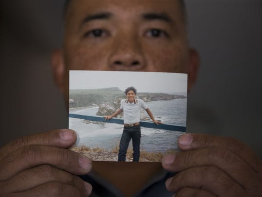 Francis Charfauros holds a photo of himself, June 14,