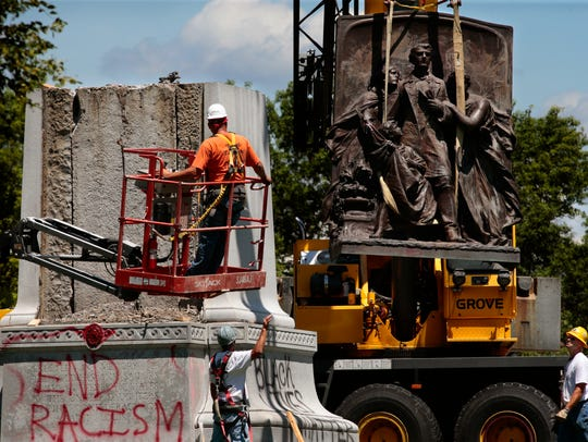 A crane removes a sculpture from a Confederate monument in Forest Park on Monday, June 26, 2017, in St. Louis.