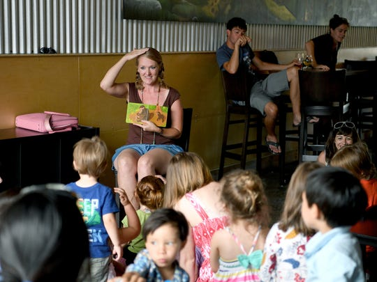 Corina Casanova reads a book to children as many of