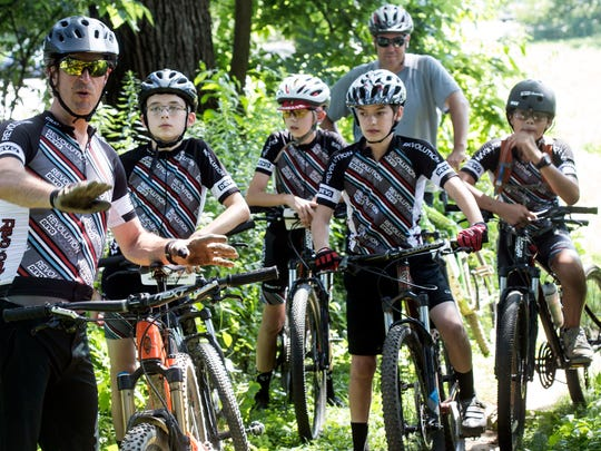 Revolution Devo Cycling coach Brian Segal provides instruction to his junior development cycle team before beginning a hill climbing exercise in Seneca Park on Sunday.