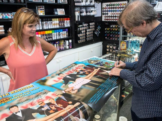 Tracy Johnson watches as magician Mac King signs a few posters for Caufield's Novelty on Wednesday afternoon. 7/12/17