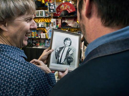 Mac King laughs at one of his old headshots kept behind the counter at Caufield's Novelty shop. 7/12/17