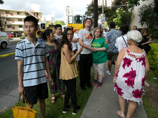 Onlookers stand on a sidewalk as a fire burns at the