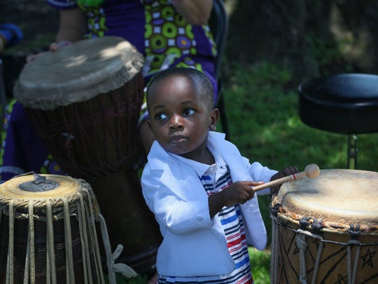 Mazani Ali, age 2, takes to the drums at a picnic in San Diego, home to the state's largest cluster of refugees.
