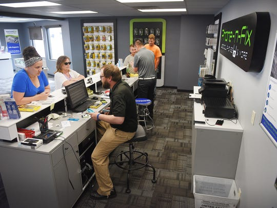 Employees work with several customers at Phone-N-Fix