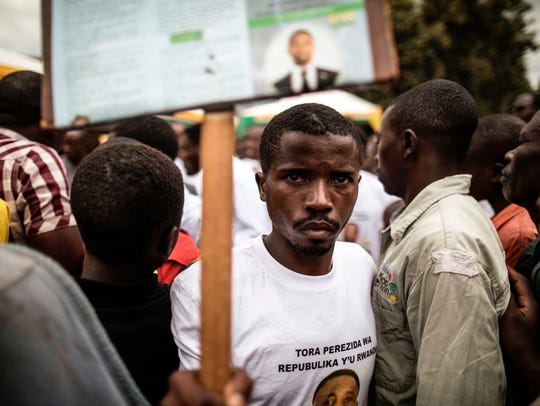 A supporter poses with a placard presidential candidate