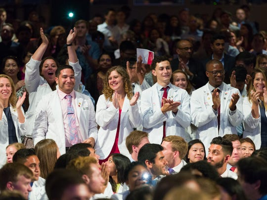 Second-year medical students at Rutgers Robert Wood Johnson Medical School cheer and congratulate new students who have just donned their white coats for the first time. The second-year students help to coordinate the ceremony and mentor the incoming students during the week of orientation leading up to the event.