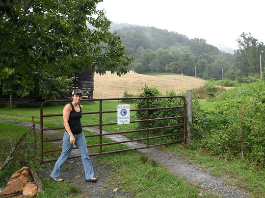 Laura Boggess closes a gate that leads to the trailhead to hike to Bailey Mountain Park in Mars Hill on Friday, Aug. 4, 2017. Current access to the trailhead involves driving more than 3 miles from town and driving through two private properties via a legal easement.