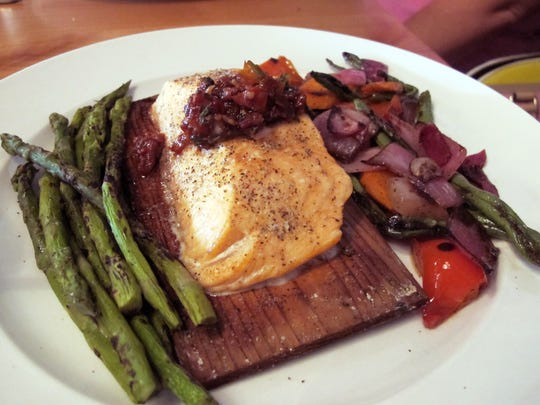 Cedar Salmon includes oven-dried tomato vinaigrette, roasted vegetables and blistered asparagus at Burntwood Tavern in Mercato in North Naples.