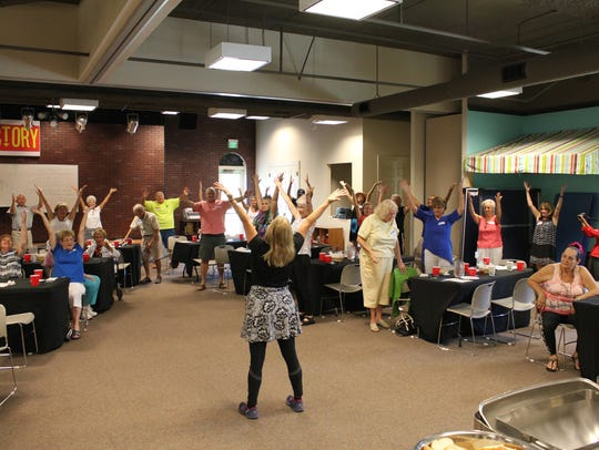 The Y's Deborah Passero leads a mild after-lunch exercise