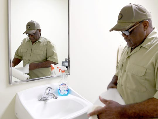 Paul Poore unravels a paper towel roll to clean a mirror in a bathroom at the Westgate Shopping Center on Wednesday, Aug. 30, 2017. Poore does a little bit of everything at the center from cleaning to maintenance to holding general knowledge about the buildings.