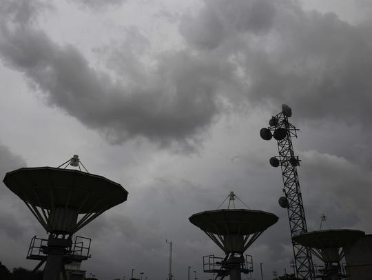 Satellite dishes are pointed toward the cloudy sky