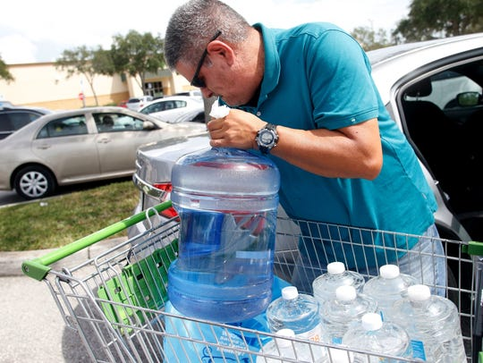 Carlos Otero, of St. Petersburg, Fla., loads his car