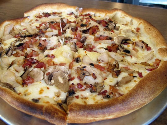 Chicken carbonara signature pizza features Alfredo sauce, Parmesan grilled chicken, mushrooms, crushed red pepper and bacon at Pie Five Pizza Co.