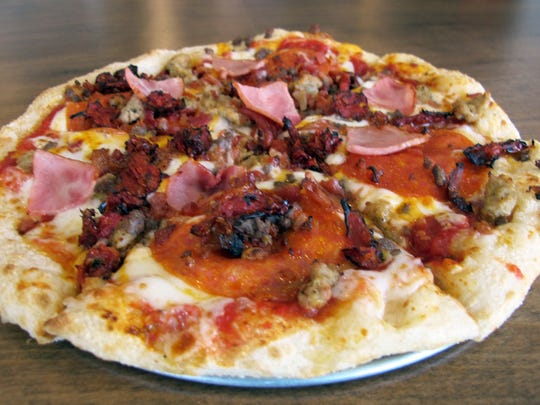 High Five signature pizza features Tuscan marinara, cheddar, pepperoni, Italian sausage, bacon, Canadian bacon and beef at Pie Five Pizza Co., 22905 Lyden Drive, across from Coconut Point in Estero.