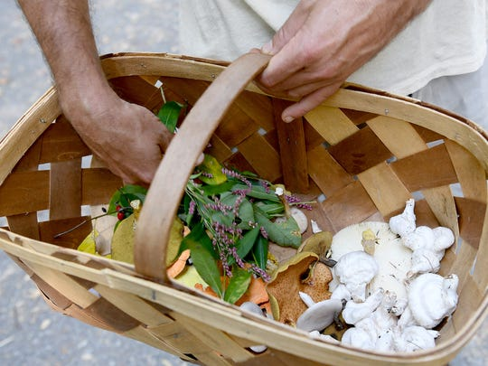 Foraging guide Alan Muskat holds a basket of foraged