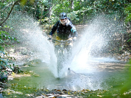 "John Cromwell splashes through a creek as he demonstrates one of the many mountain biking trails in the Bent Creek Experimental Forest on Wednesday, Sept. 27, 2017. ""It just gets in your blood,"" the 67-year-old said about getting back on a mountain bike after a long hiatus about four years ago."