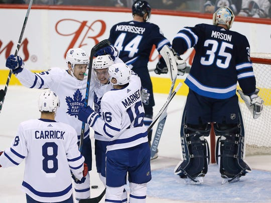 Toronto Maple Leafs' Connor Carrick (8), James van Riemsdyk (25), Tyler Bozak (42) and Mitchell Marner (16) celebrate van Riemsdyk's goal against the Winnipeg Jets during the first period of an NHL hockey game, Wednesday, Oct. 4, 2017 in Winnipeg, Manitoba. (John Woods/The Canadian Press via AP)