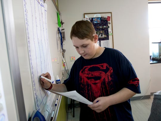 Aiden Rothlisberger writes down his findings during a science class Tuesday at Hermosa Middle School in Farmington.