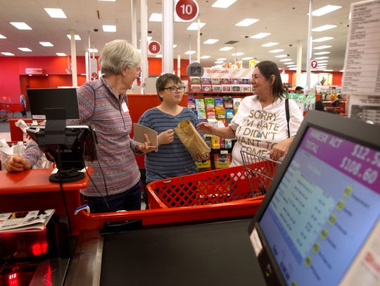 Volunteer Jenny Coffey, left, talks with Robert Coffman and his grandmother Jerri Coffman about their purchases Thursday during the Rio del Sol Kiwanis Club's Clothes for Kids event at Target in Farmington.