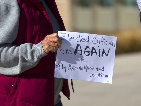 Aztec City Commissioner Katee McClure, acting as a private citizen, holds a sign on Monday at the Bureau of Land Management Farmington Field Office.