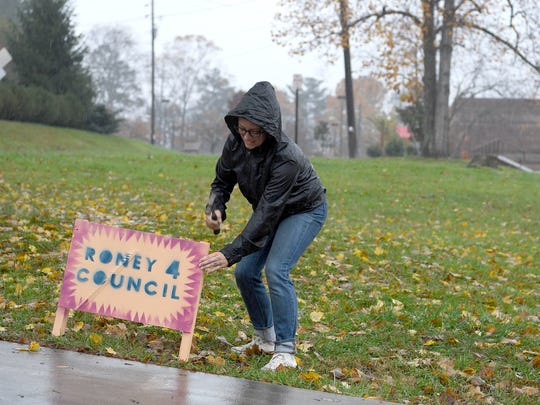 Asheville City Council candidate Kim Roney hammers one of her campaign signs into the ground outside of Vance Elementary School as rain pours down on Tuesday, Nov. 7, 2017.