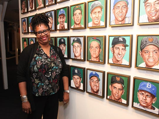 "Pat Moore, widow of artist Andy Jurinko, beside his 76 portraits of ""New York City's Golden Boys"" displayed in the Yogi Berra Museum & Learning Center."