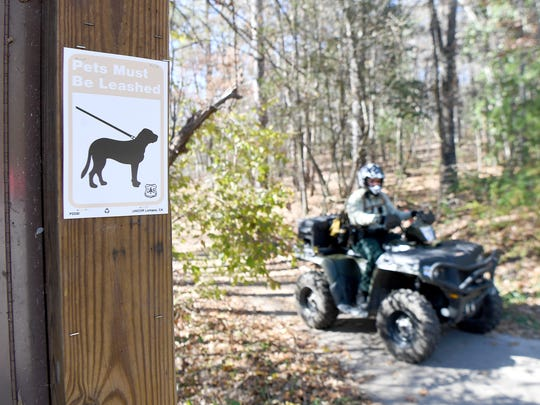 A Forest Service Law Enforcement officer rides an ATV back to the Rice Pinnacle trailhead of the Bent Creek Experimental Forest as he searches for hikers with dogs not on a leash on Friday, Nov. 17, 2017. Forest Service law enforcement is ramping up enforcement of the leash law and writing tickets to the owners of non-leashed offenders.