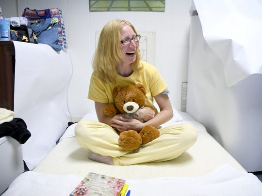 "Pam Pressley laughs as she hugs a teddy bear jokingly named ""Ray, Ray"" after her boyfriend as she sits on her bed in the basement of Grace Episcopal Church where she and about 10 other women were spending a week of nights with the Room in the Inn program on Thursday, Nov. 16, 2017. Pressley's boyfriend is currently finding shelter at the Salvation Army while she stays with the women-only program."