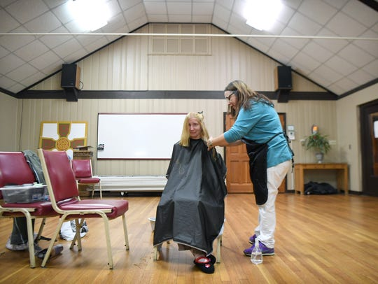 Pam Pressley gets a haircut from volunteer Lesley Barkett