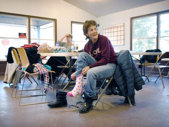 Pamela Hamrick takes off her shower shoes and puts on socks and boots at AHOPE day center to prepare to go to a church for the night with the Room in the Inn program on Thursday, Nov. 16, 2017.