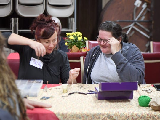 Volunteer Kelly Wedall, left, and Cathy Garrison make jewelry with volunteer Nicki Door (not pictured) at Grace Episcopal Church as she stays the night with the Room in the Inn program on Thursday, Nov. 16, 2017.  After dinner in the program the churches the women stay at provide some sort of fellowship such as crafts, nail painting, hair cutting, and games.