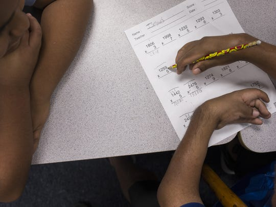 David Solano (right) works with Ismael Viera Fonseca on a math problem in their classroom at Palm Lane School in Phoenix.