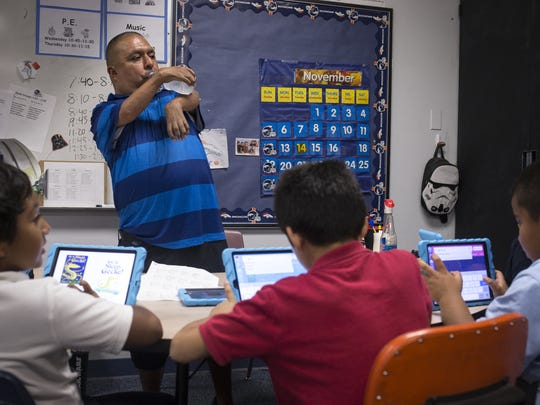 David Solano sips water while working with students in his classroom at Palm Lane School in Phoenix.