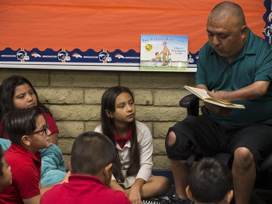 """David Solano reads R.L. Stine's """"How to Kill a Monster"""" to his fourth-grade students at Palm Lane School in Phoenix."""
