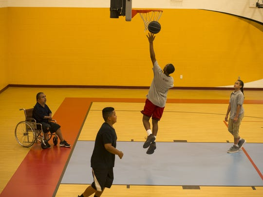 David Solano (left) watches Takhari Williams make a layup during practice at Raul H. Castro Middle School in Phoenix.