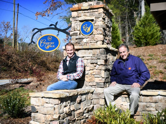 Son and father team Kevin and Ken Jackson pose at the entrance of one of their under construction developments, Country Walk, in Fletcher on Monday, Nov. 20, 2017. The Jackson family has been building and developing properties in Western North Carolina for five generations.