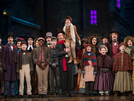 """The cast surrounds Jonathan Wainwright (Scrooge) and Ashley Bock (Tiny Tim) in """"A Christmas Carol,"""" performed by Milwaukee Repertory Theater."""