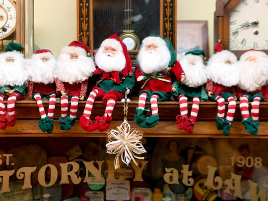 A line of Santas sits on a cabinet in the living room